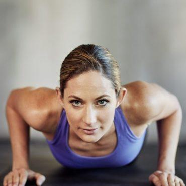 Shot of an attractive young woman doing pushups as part of her workout